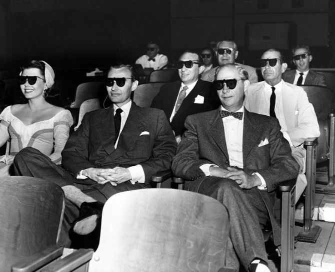 "In 1953, MGM offered its first (and only) film in the then-popular 3D format, ""Kiss Me Kate."" The original stage show's composer, Cole Porter, tries out his 3D glasses here (second row, far right) along with (front row, from left) the movie's star Ann Miller, stage producer Lemuel Ayers, and singer George Byron, along with (second row) producer Jack Cummings."
