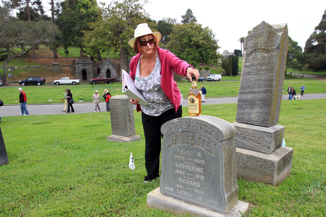 "Barbara Gibson places a bottle of Yukon Jack's namesake hooch at the tomb of Leroy Napoleon ""Jack"" McQuesten."