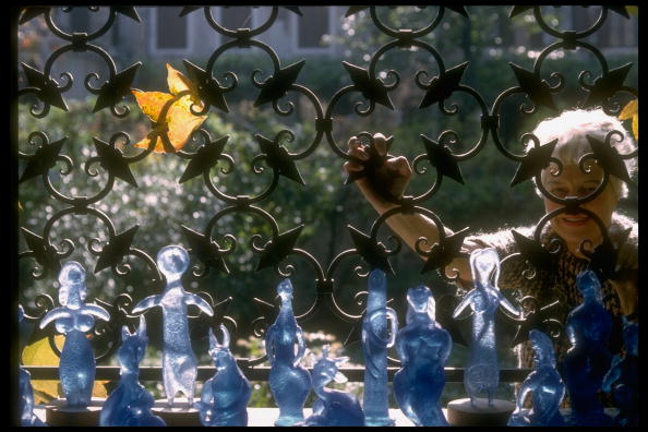 Peggy Guggenheim at her palazzo, peeking through an elaborate wrought iron fence, with glass figures designed by Picasso. Credit: David Lees/The LIFE Images Collection/Getty Images