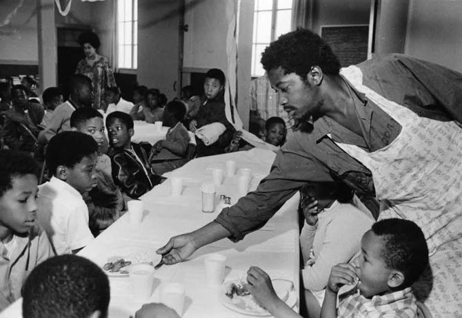 Charles Bursey hands plate of food to a child seated at Free Breakfast Program. Credit: Courtesy of Pirkle Jones and Ruth-Marion Baruch/theblackpanthers.com.