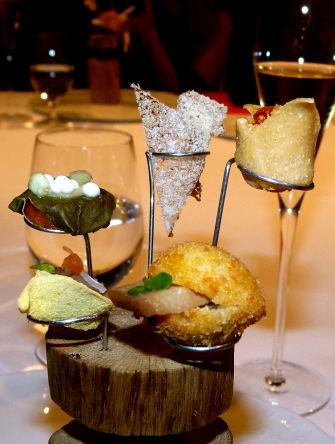 A group of appetizers that represent international dishes that have impressed Joan Roca and his brothers. The tastes were from Mexico (a miniature burrito with mole poblano and guacamole), Peru (ceviche broth), China (pickled vegetables with plum cream), Morocco (goat yogurt with almond slivers, honey, saffron, ras el hanout, and rose petals), and from Korea (panco fried bread, bacon with soja sauce, snow peas, kimchi, and sesame oil). (Photo by Manos Angelakis, Epoch Taste)
