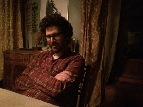 Josh Marston, on set, at the dining room table.