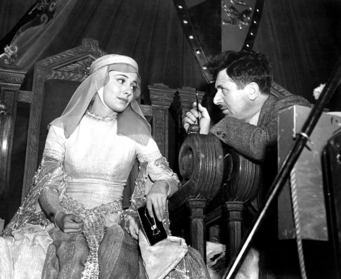 OLIVIA DE HAVILLAND is given some last minute lighting by cameraman SOL POLITO for ADVENTURES OF ROB